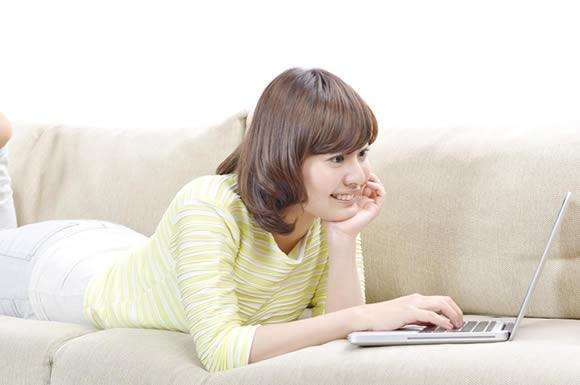 寝そべりながらパソコンを見る女性