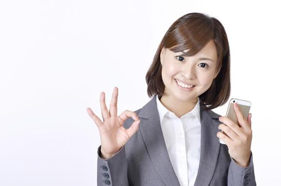 アイフォンを手に持つ女性