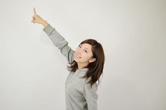 指をさして上げる女性