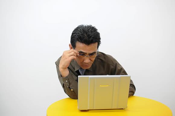 パソコンを見て肩こりな男性