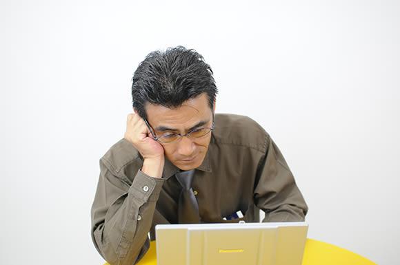 パソコン見て悩む男性